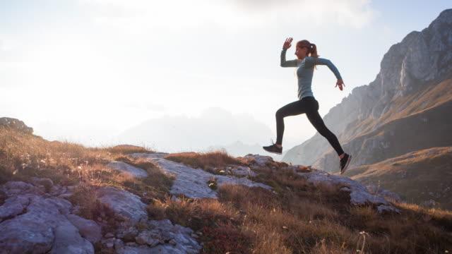 vidéos et rushes de athlète conscient de corps d'athlète courant à l'extérieur dans la nature dans le terrain de montagne - performance athlétique