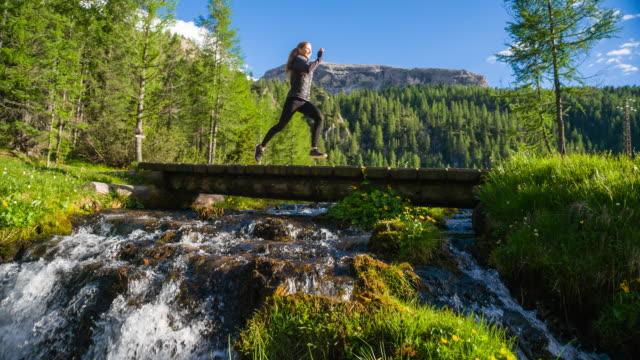 Körper bewusst Frau läuft auf einem Pfad auf einer Wiese über Bach