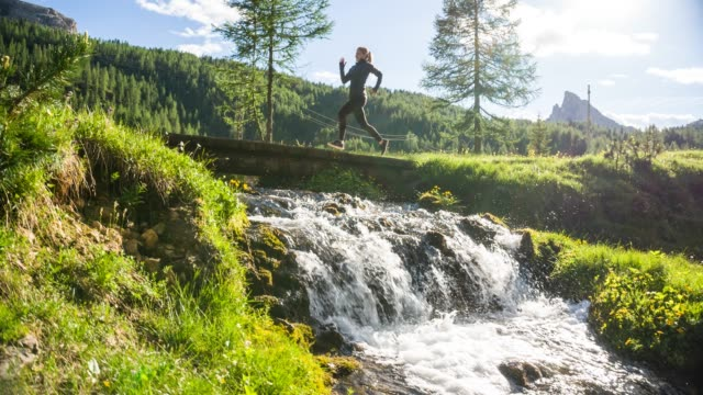 body conscious woman running on a trail on a meadow over stream - fiume video stock e b–roll