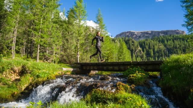 vidéos et rushes de femme conscient de corps courant sur un sentier sur un pré au-dessus du ruisseau - joggeuse