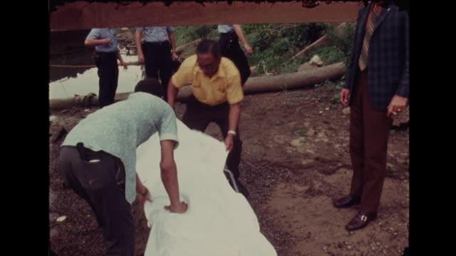body floating in water under bridge body put in body bag taken away in ambulance - selbstmord stock-videos und b-roll-filmmaterial