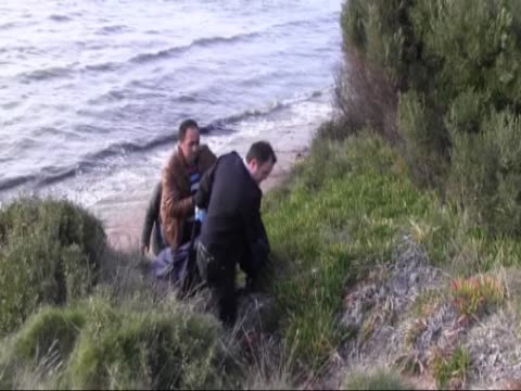 body of a child refugee washes ashore at aegean sea in didim district of aydin western turkey on february 11 2016 according to officials 8yearold... - aydın province stock videos and b-roll footage