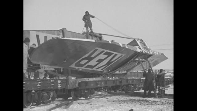 body of fokker airplane unloaded from train car with men holding up back end of plane / men set plane end down in snow / man stands on roof of... - exploration stock videos & royalty-free footage