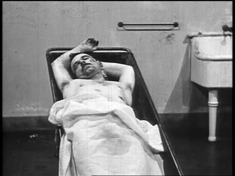 b/w 1934 body of john dillinger lying sprawled under sheet on table in morgue - john dillinger stock-videos und b-roll-filmmaterial