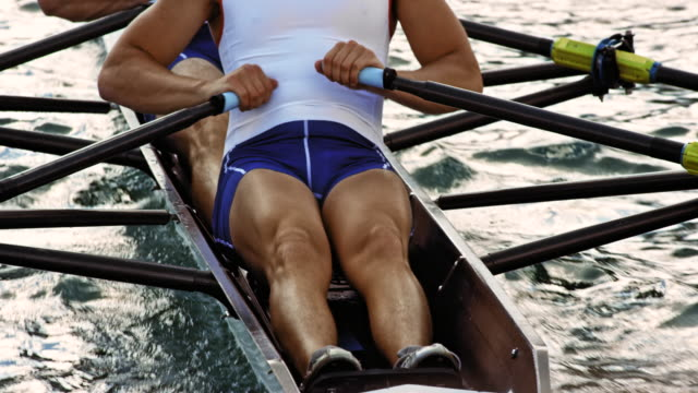 Body of rower gliding on a lake with his team mate in a double scull