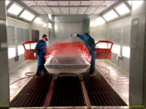 body of sports car being spraypainted bright red / detroit, michigan - chassis stock videos & royalty-free footage