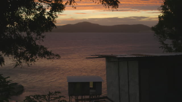 body of water and mountains during sunset - gebäudefries stock-videos und b-roll-filmmaterial