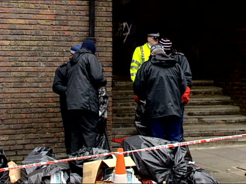 body parts found in london: suspect named; itn england: london: camden: ext police officer searching thru bin bags after discovery of body parts gv... - 防水シート点の映像素材/bロール