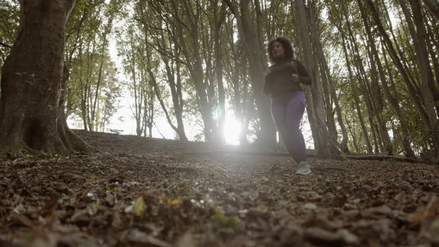 body positive black female running exercising outdoors in forest, plus size obese overweight black woman jogging sports training - hourglass stock videos & royalty-free footage
