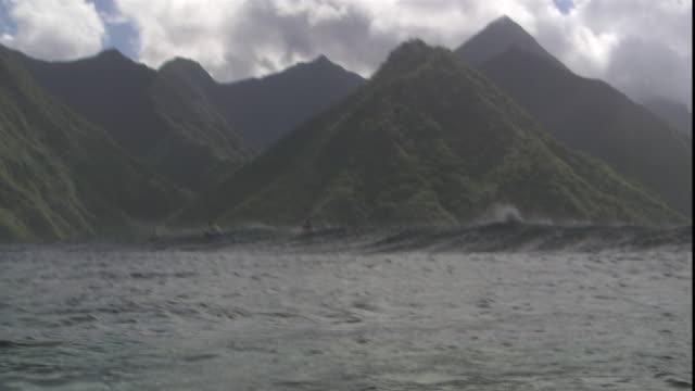 bodyboarders ride waves off the coast of teahupoo. - tahiti stock videos & royalty-free footage
