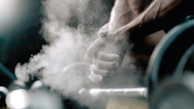 vídeos de stock e filmes b-roll de super slo mo bodybuilder claps with hands full of sport chalk - body building