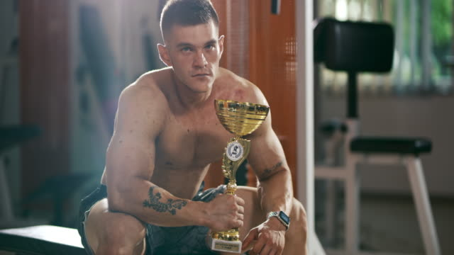 slo mo bodybuilder showing a trophy - gold medalist stock videos & royalty-free footage