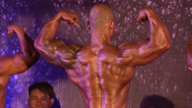 bodybuilders pose during the latchford classic bodybuilding competition in bangkok, thailand. - 三角筋点の映像素材/bロール