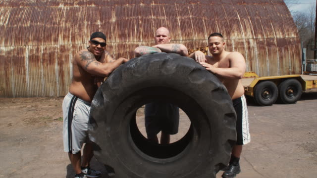 MS Bodybuilders posing behind giant truck tire, Middletown, Connecticut, USA