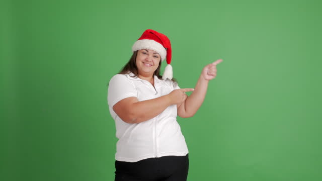 vídeos y material grabado en eventos de stock de cuerpo las mujeres. chica gorda en santa sombrero muestra copia espacio y pulgar para arriba sobre fondo verde - camiseta blanca