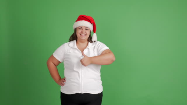 körper-positive frauen. dickes mädchen in nikolausmütze zeigt textfreiraum und daumen oben auf grünem hintergrund - weihnachtsmütze stock-videos und b-roll-filmmaterial