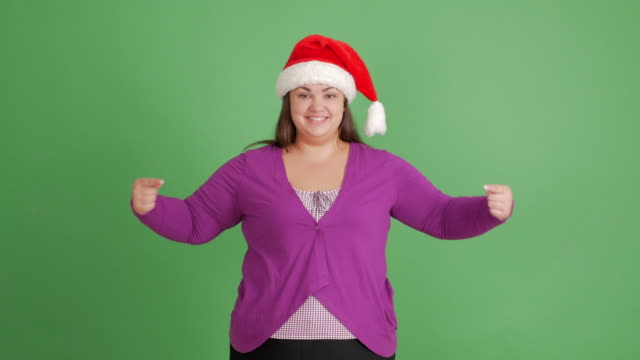 Body-Positive Women. fat girl in santa hat shows copy space and thumb up on green background