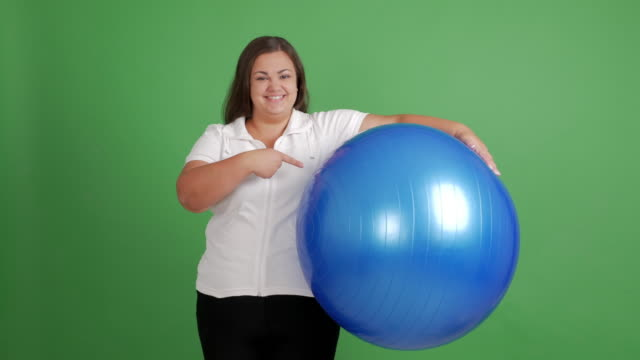 Body-Positive Women. full beautiful woman with a ball showing copy space on a green background