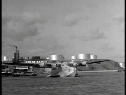 boeing 314 'clipper' in harbor people exiting small boat onto dock clipper bg people walking on large ramp toward building 'aeroporto maritimo de... - flugpassagier stock-videos und b-roll-filmmaterial