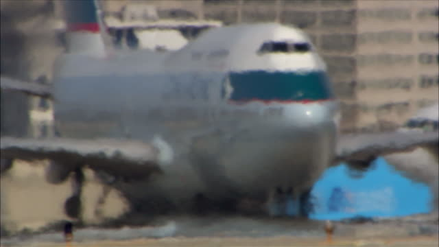 A Boeing 747 taxis on a tarmac through heat waves at LAX International.
