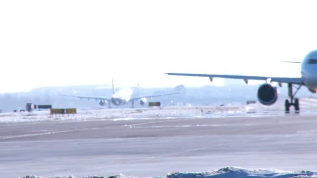 boeing 767 flugzeug taxis mit a320 takoff-winter - start  und landebahn stock-videos und b-roll-filmmaterial
