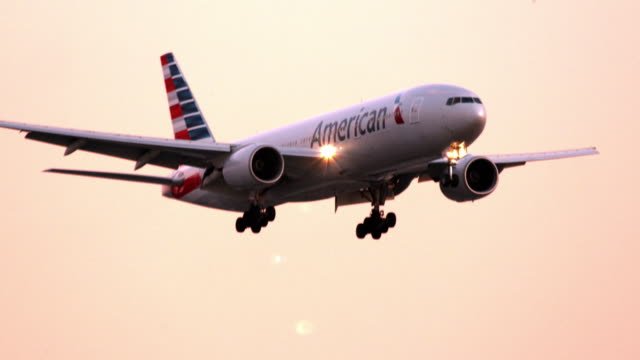 ls pan boeing 777 wide-bodied twin-engine american airlines jetliner on landing approach against sunset sky background / los angeles, california, usa - 旅客機点の映像素材/bロール