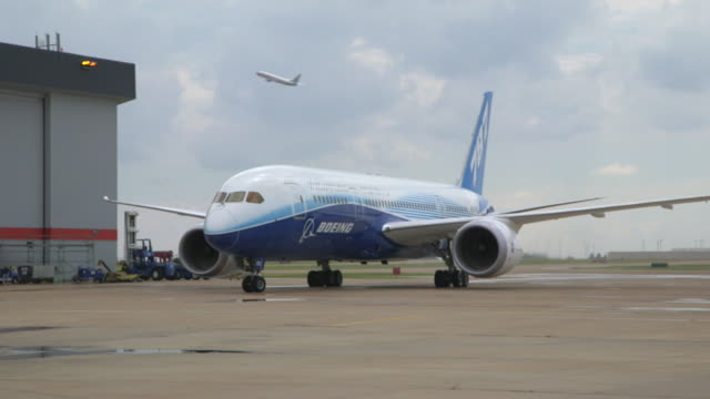 vidéos et rushes de boeing 787 dreamliner taxis to stop outside hanger/dfw international airport, dallas-fort worth, texas, usa - macadam
