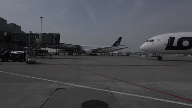 a boeing 7878 dreamliner aircraft operated by lot polish airlines sa manoeuvres on the tarmac at warsaw chopin airport in warsaw poland on saturday... - fluggastbrücke stock-videos und b-roll-filmmaterial