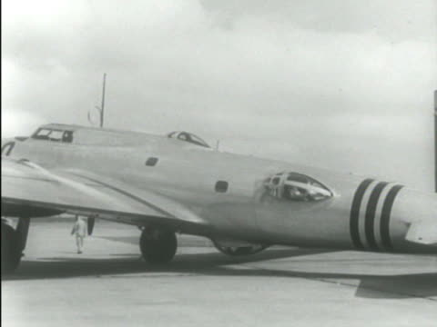 boeing b17 'flying fortress' being pulled slowly out of hangar men driving small open bomb carts toward angle parked b17s ws b17 bomb bay doors... - boeing b 17 bildbanksvideor och videomaterial från bakom kulisserna