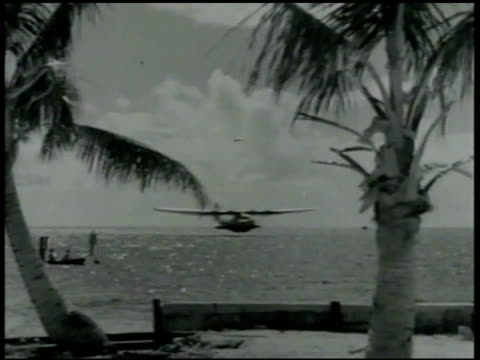 Boeing B314 'Clipper' airplane landing at sea palm trees FG WS Marines Navy sailors people outside 'Pan American Airways System' building Philippines...