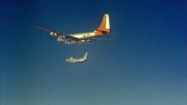 AIR TO AIR Boeing B-50 Super fortress strategic bomber with Scout X-2 rockets and chase airplane flying against blue sky