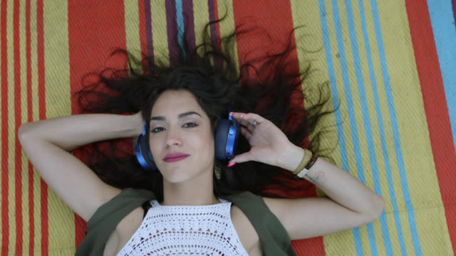 slo mo. a bohemian hipster woman is lying on a boho blanket listening to music on blue headphones - boho stock videos & royalty-free footage