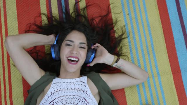 slo mo. a bohemian hipster woman is lying on a boho blanket listening to music on blue headphones - ヘッドフォン点の映像素材/bロール