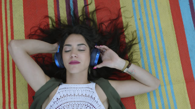a bohemian hipster woman is lying on a boho blanket listening to music on blue headphones - boho stock videos & royalty-free footage