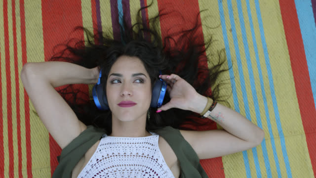 slo mo. a bohemian hipster woman is lying on a boho blanket listening to music on blue headphones - listening stock videos & royalty-free footage