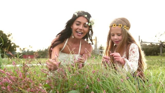 vidéos et rushes de boho chic femme et petite fille cueillait des fleurs minuscules - robe d'été