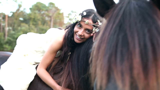 boho chic woman sitting on chestnut brown horse - boho stock videos & royalty-free footage