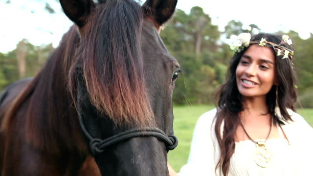 Boho chic woman standing with chestnut brown horse