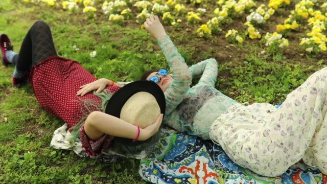 boho girls lying down on the grass and enjoying - boho stock videos & royalty-free footage
