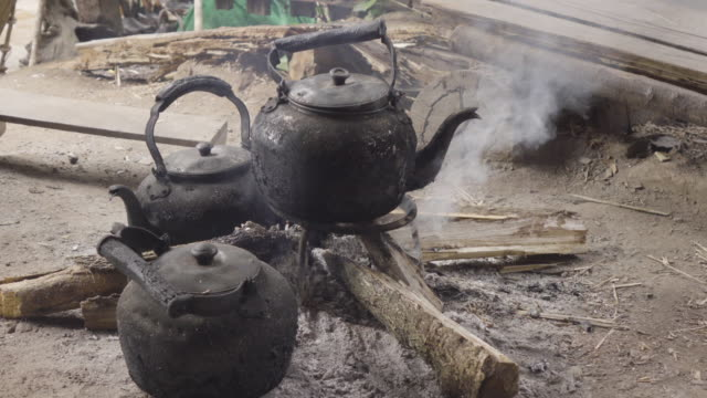 Boil Water Using Black Kettle On Simple Stove With Firewood.