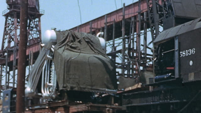 Boiler on flatcar moving alongside open framework of USS Yorktown under construction and crane lifting boiler and workers into the air / Newport News...
