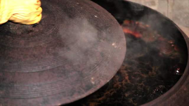 boiling soy sauce in an iron pot - tradition stock-videos und b-roll-filmmaterial