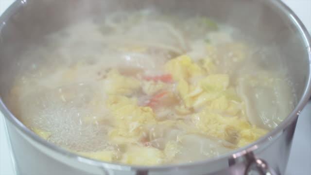 boiling tteok mandu guk (korean rice cake soup with dumplings) - korean new year stock videos & royalty-free footage