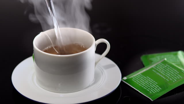 vidéos et rushes de  ms boiling water being poured onto tea bag in white teacup / los angeles, california, united states - thé boisson chaude