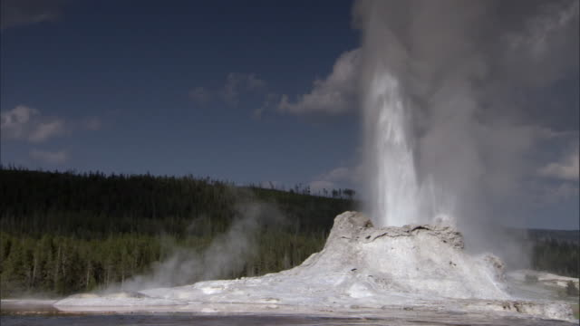boiling water ejects from erupting castle geyser, yellowstone, usa - geysir stock-videos und b-roll-filmmaterial