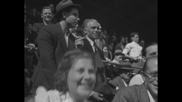 Boisterous crowd sitting in sun at Ebbets Field in Brooklyn New York City / enthusiastic yelling man with glasses wearing shirt and loosened tie...