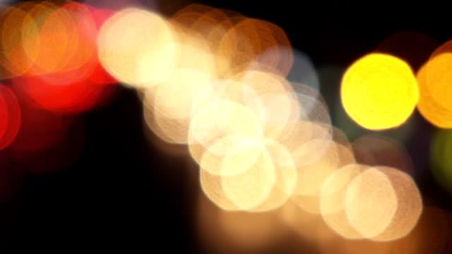 vídeos de stock e filmes b-roll de bokeh of car in city at night - farol luz de veículo
