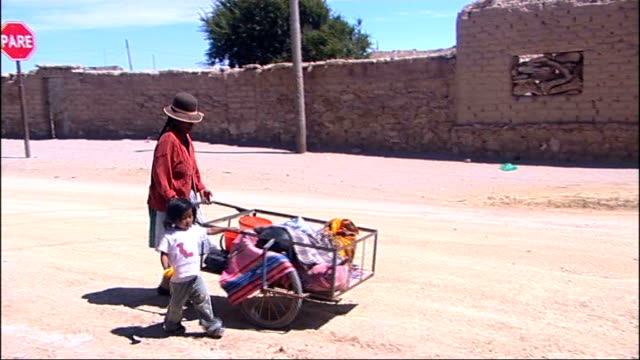 Bolivia is the site of large reserves of lithium likely to be main resource of future Bolivian woman pushing handcart along past next little girl