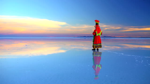 bolivian woman at sunrise in traditional national clothing - ウユニ塩湖点の映像素材/bロール