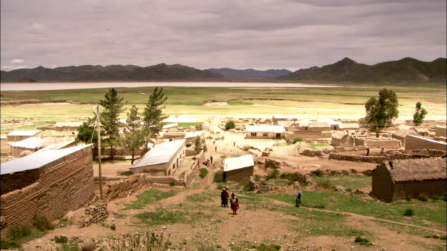 bolivians walk up a hill above adobe buildings set on wide plains. available in hd. - adobe stock videos & royalty-free footage